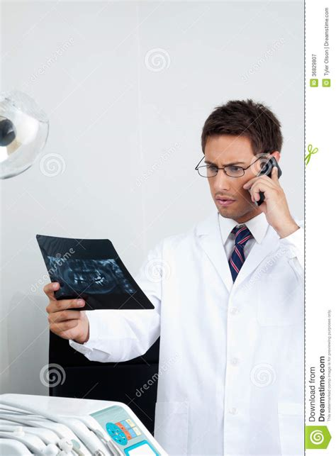 cell phone clinic dentist on call as he checks x report royalty free