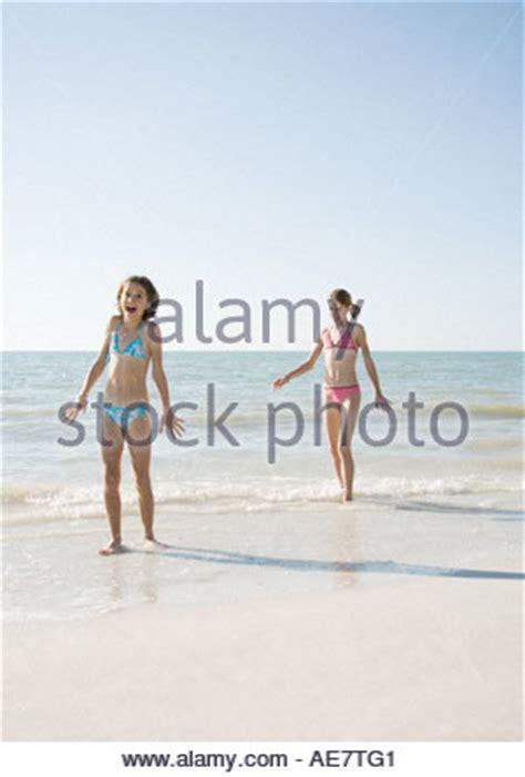 Preteen Girl In Bikini Standing On Rock Looking Into