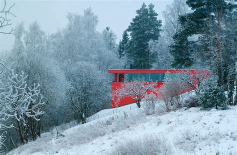 bright red house nestled   norwegian river valley