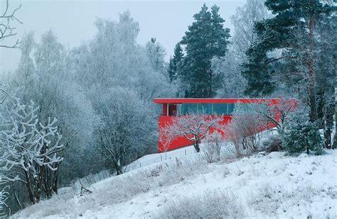 bright red house nestled   norwegian river valley