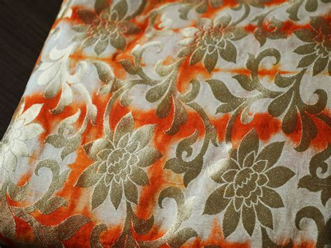 brocade fabric  beige orange  gold motifs pattern