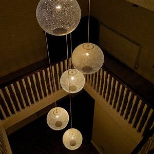A cluster of white rita pendant lights over stairwell