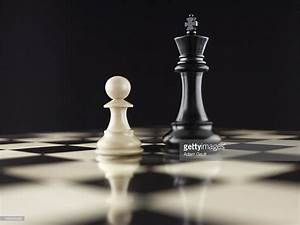White Pawn Chess Piece Facing Black King On Chess Board ...