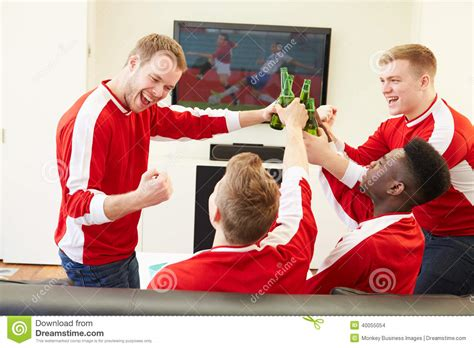 type of sport that fans watch on tv on thanksgiving group of sports fans watching game on tv at home editorial