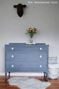 A Grey-blue-purple Dresser With Soft Blue Knobs