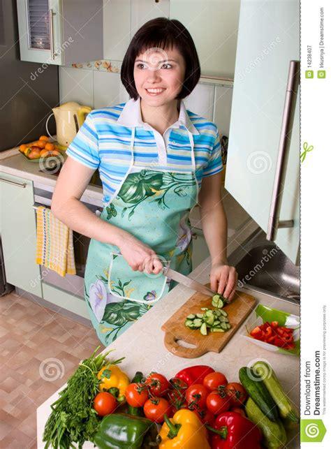 femme a la cuisine légumes de découpage de femme dans la cuisine