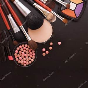 Various makeup products on dark black background with ...