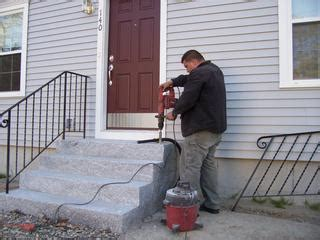 installing wrought iron handrails into granite steps