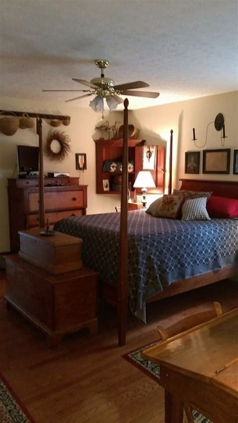 high poster bed warm wood cozy bedroom primitive bedroom