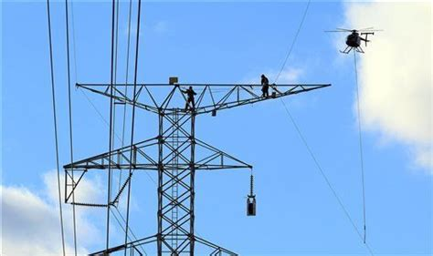 workers dangling  helicopters  install power lines