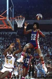 Julius Erving flies to catch and dunk an alley-oop pass ...