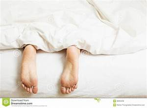 Womans, Feet, Sticking, Out, Of, Blanket, On, Bed, Stock, Image