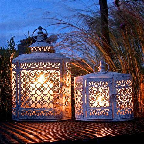 pair of white oval filigree lanterns by garden