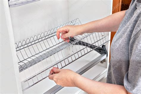installing wire dish rack  drying dishes  kitchen cabinet stock photo  grigvovan