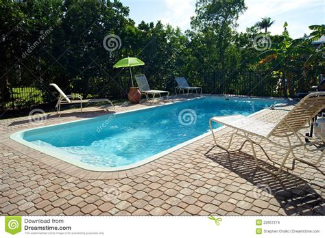 rectangular swimming pool with deck chairs stock photo