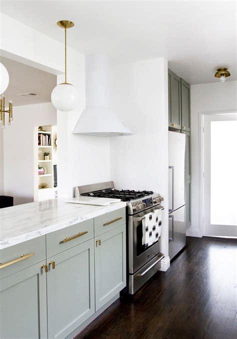 una cocina de ikea en verde claro  blanco abierta al