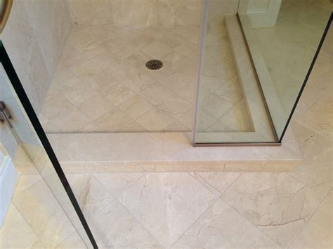 solid slab crema marfil  shower curb  grout lines