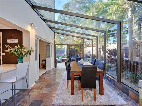 All glass conservatory blends well with the garden for a