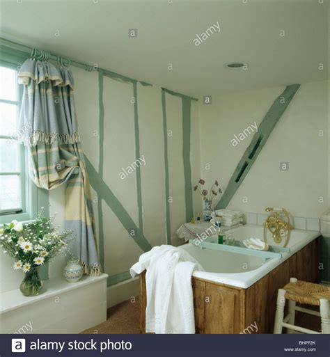 Painted Pastel Green Beams On Wall Of Small White Cottage