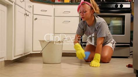 A Young Woman Scrubs Her Kitchen Floor Royaltyfree