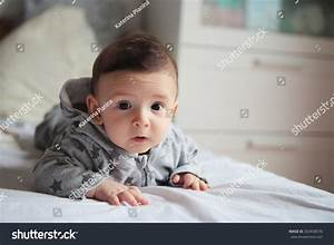 Small Baby Crawling On The Bed In White Room.On His Face ...
