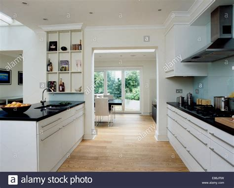 granite topped kitchen island wooden flooring in large modern kitchen with doorway to