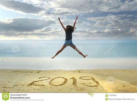 New Year 2019 On The Sand,happy Girl With Hands Up Jumping
