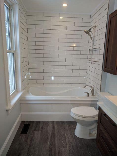 simple bathroom  attic dark floors white subway tile