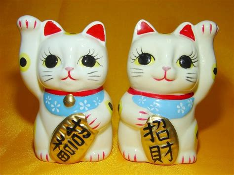 pair of lucky cat statues left hand up and right paw up