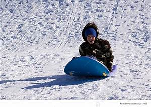 Image Of Little Boy Sledding Down The Hill