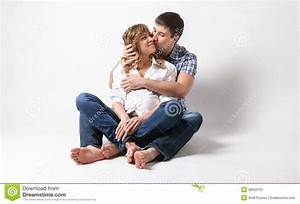 Pregnant woman sitting on floor and being kissed by for Sitting on the floor during pregnancy