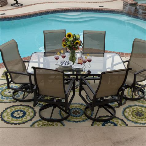 outdoor glass patio table acadia 7 piece sling patio dining set with swivel rockers