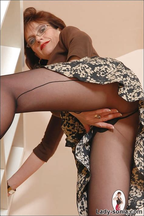 leggy mature lady in glasses teasing her twat through her pantyhose