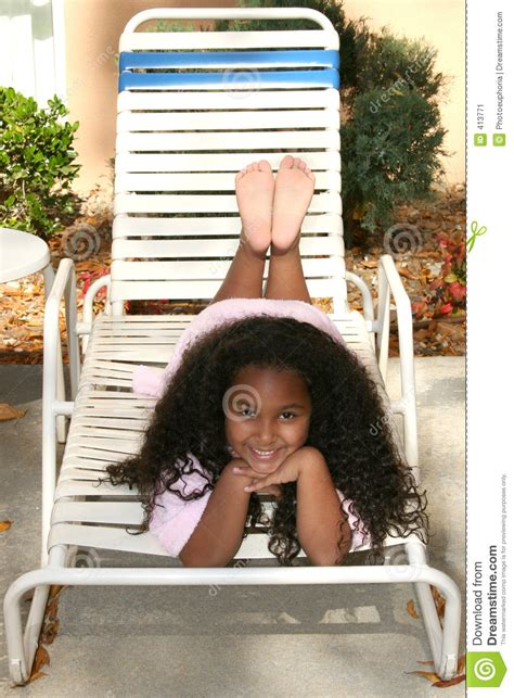 girl  pool robe laying  lounge chair stock image