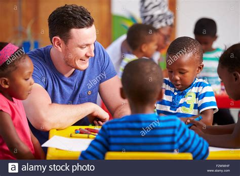 cape town township stock photos amp cape town township 961 | volunteer teacher sitting with preschool kids in a classroom F2WWHF