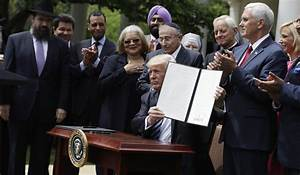 President Donald Trump holds a signed executive order ...
