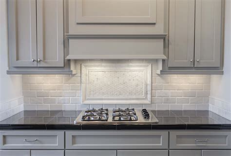grey painted cabinets with white marble pillowed subway
