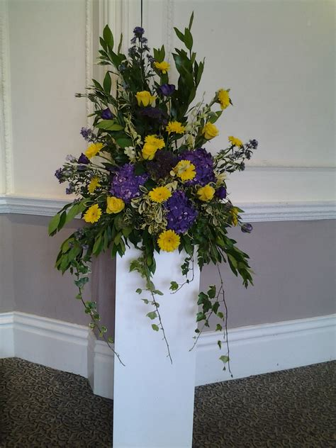 purple  yellow pedestal arrangement church flowers