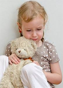 Sad lonely little girl sitting with teddy bear near stock ...