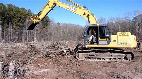 john deere  excavator stacking brush youtube