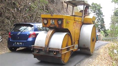 Driving Road Roller On Busy Road