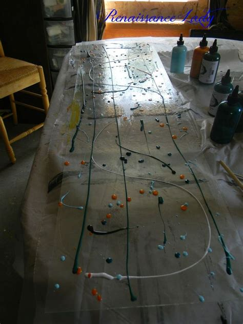 She Lays Out A Large Pane Of Glass, Drips Spots Of Colored
