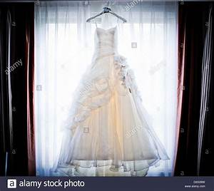 photo of a beautiful white wedding dress hanging up in a With hanging wedding dress