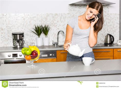Talking Kitchen by Cheerful Talking On The Phone In Kitchen Stock