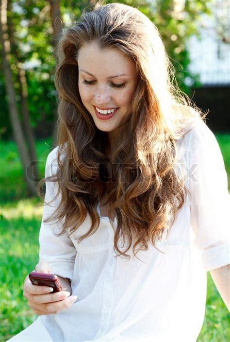 junge huebsche frau liest sms auf dem stockfoto