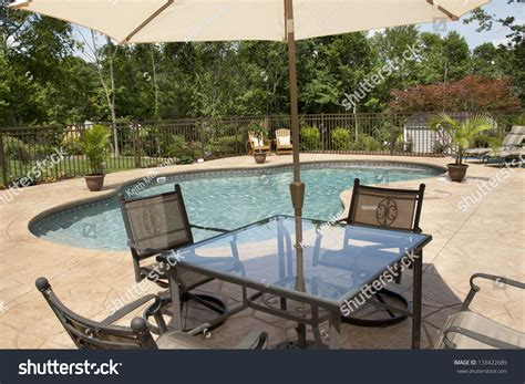a view of a luxury salt water pool and patio in a