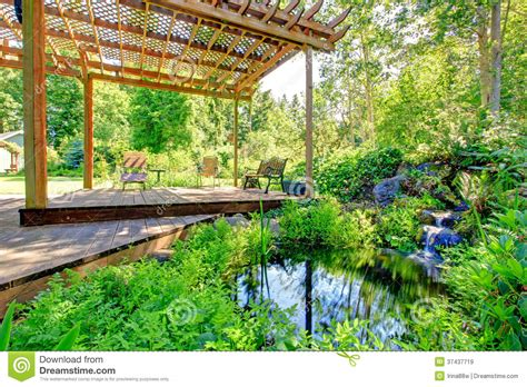 Picturesque Backyard Farm Garden With Small Pond And Patio