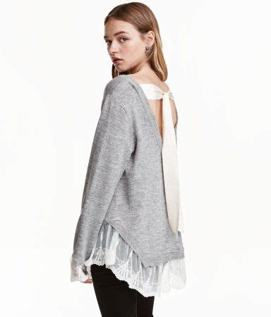 gray sweater in a soft knit low cut v neck at back with ties at back of neck