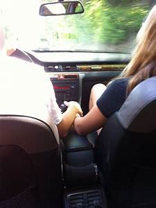 Boyfriend and girlfriend holding hands while driving in a ...