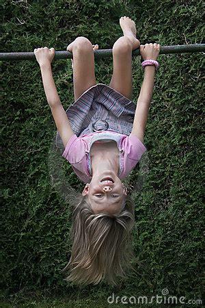 child hanging upside   climbing frame stock